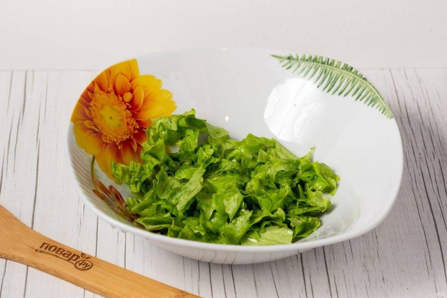 Листья салата порвите руками и положите в салатник.