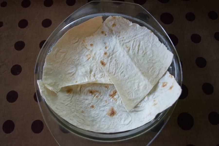 Тонкий лаваш выкладываем в смазанную маслом форму в один слой. Лаваш удобнее нарвать на части и из кусочков собрать единый корж.