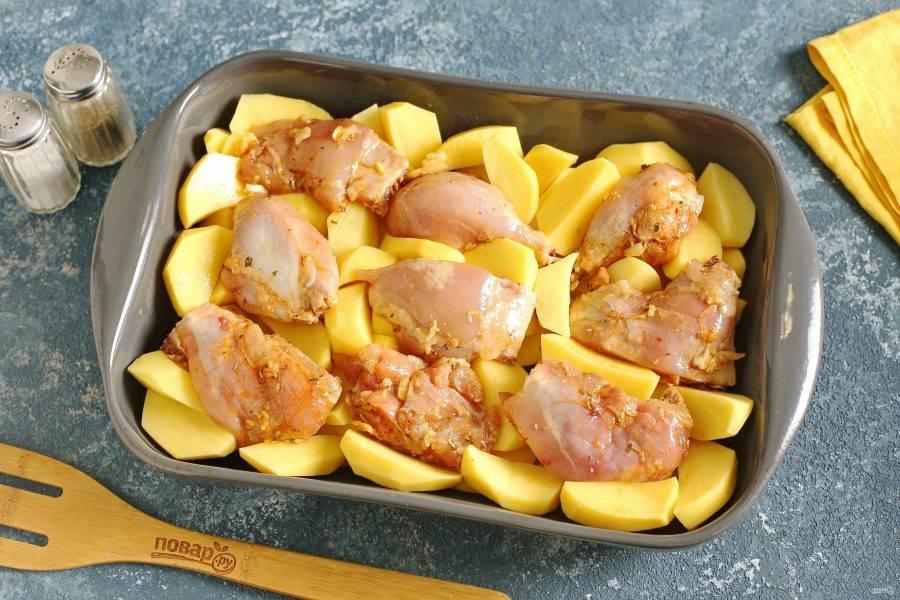 Форму для запекания смажьте маслом. Выложите равномерно картофель, а сверху распределите кусочки курицы.
