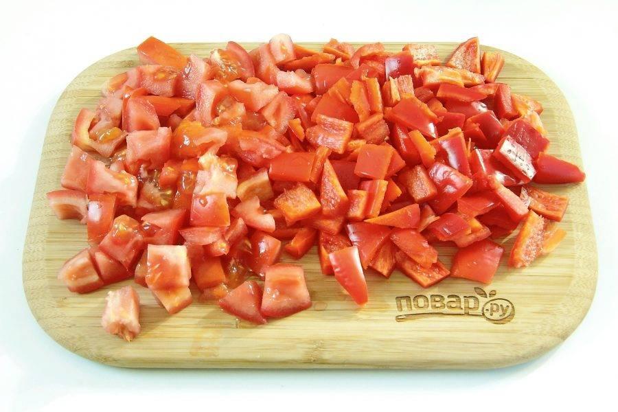 Нарежьте крупными кубиками помидоры и перец.