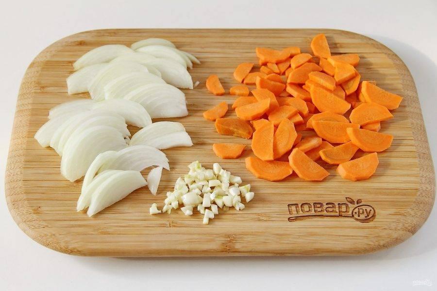 Тем временем, нарежьте крупно морковь и лук. Чеснок измельчите кубиками при помощи ножа.