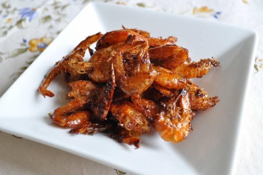 Готовые сушеные креветки получаются медово-румяными, хрустящими и очень вкусными. Можете подать с острым или кисло-сладким соусом, например. Приятного аппетита!