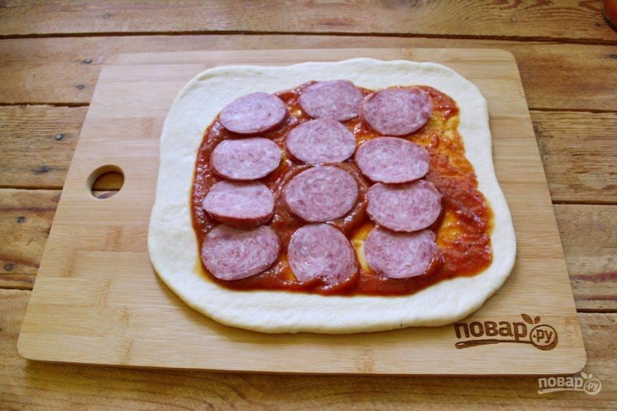 Теперь выкладываем начинку: сыр, колбасу, специи. Начинка может быть любой, на ваш выбор. Такую пиццу обычно готовят с колбасой или ветчиной, но встречаются варианты пиццы из овощей или с грибами. Тут выберите на свой вкус. Отмечу лишь, что пицца будет запекаться около 40  минут, но начинка, которую вы кладете в пиццу, должна быть уже готовой. В противном случае начинка не успеет пропечься.