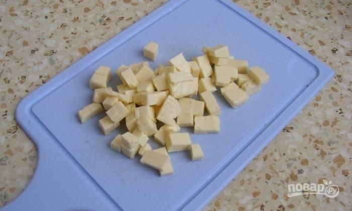 Мелко нарежьте сыр. Добавьте его в крем-суп. Поставьте кастрюлю на медленный огонь. Ещё раз пройдитесь блендером до единой консистенции и вскипятите.