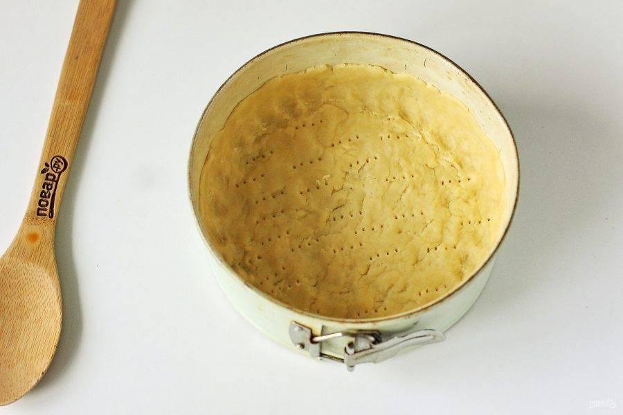 Достаньте тесто и распределите его по смазанной маслом форме, формируя руками высокие бортики. Наколите тесто вилкой и отправьте в разогретую до 200 градусов духовку на 15-20 минут.