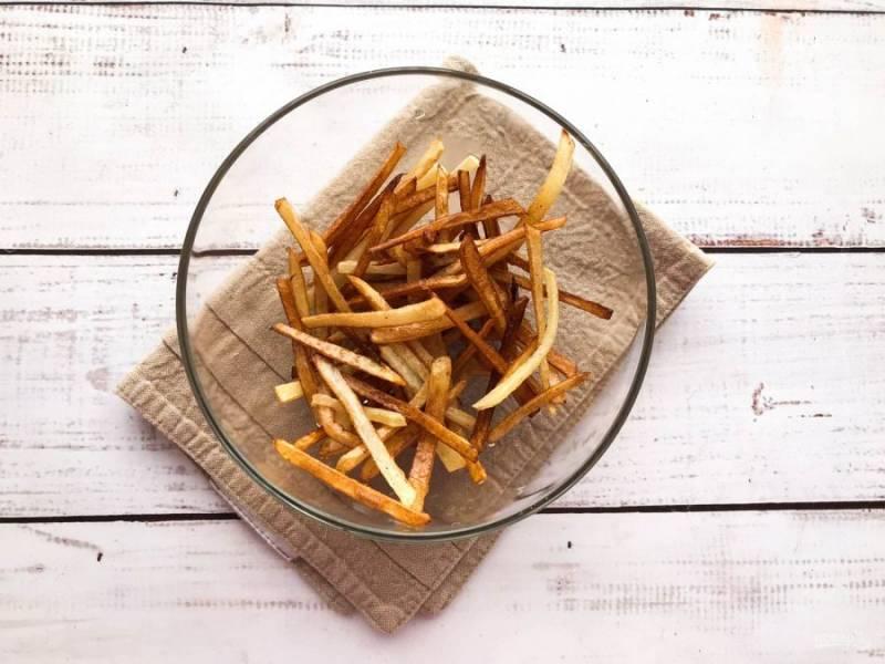 Картофель хорошо помойте, очистите, нарежьте соломкой, обжарьте на хорошо разогретой сковороде с растительным маслом и выложите в глубокую тарелку.