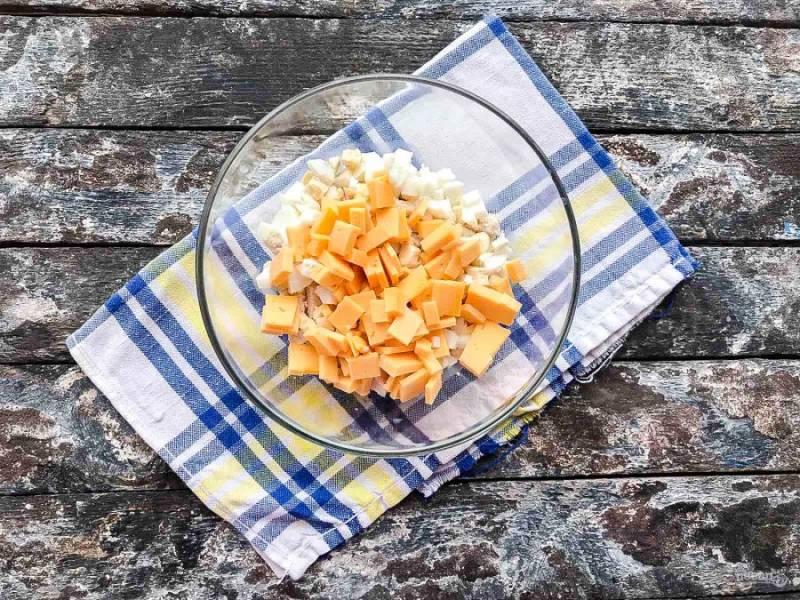 К курице добавьте нарезанный кубиками твердый сыр.