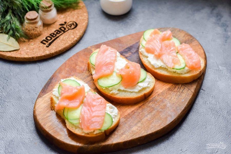 Форель нарежьте тонкими пластинами и выложите на бутерброды.