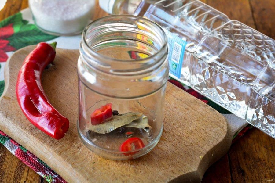 На дно простерилизованной пропаренной банки сложите кусочки острого перца и лаврового листа. Также добавьте пару горошин черного перца.