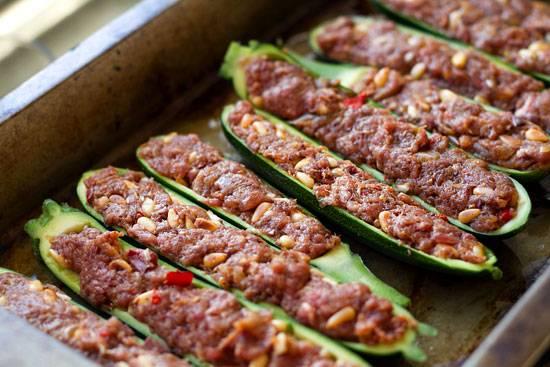 """2. Кабачки натираем солью. В блендере измельчаем лук, перец чили, болгарский перец, чеснок. Дальше добавим овощное пюре в фарш, перемешаем. В последнюю очередь добавим порезанные оливки и кедровые орешки. Специи - по вкусу. Фаршируем смесью """"лодочки""""."""