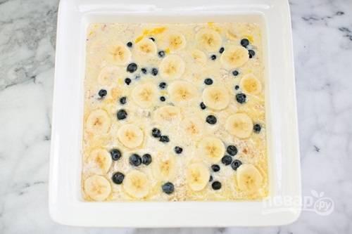 Взбиваем яйца с молоком и растопленным сливочным маслом и аккуратно равномерно заливаем смесь поверх овсянки. Выкладываем оставшиеся бананы и чернику.