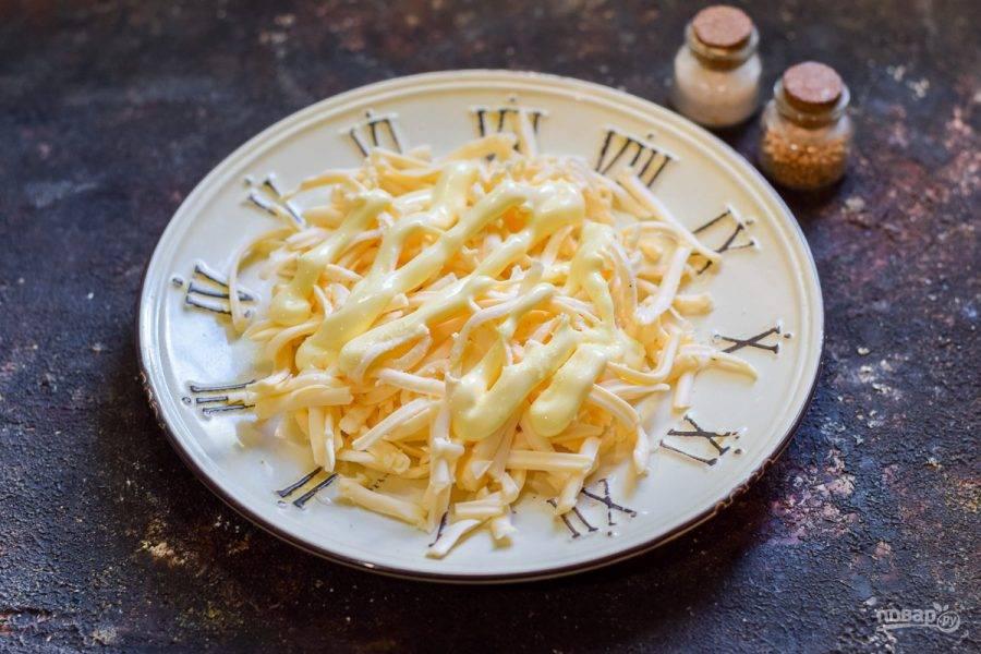 Плавленый сыр натрите на средней терке, смажьте слой сыра майонезом и пропущенным через пресс чесноком.