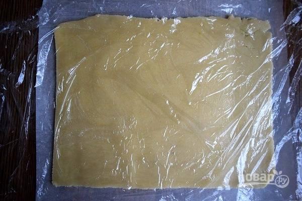 Тесто разделите на 4 равные части. Каждую раскатайте в прямоугольник размером 18х25 см., наколите вилкой. Раскатывайте сразу на пергаменте для выпечки через пищевую пленку. Обрезки также раскатайте.