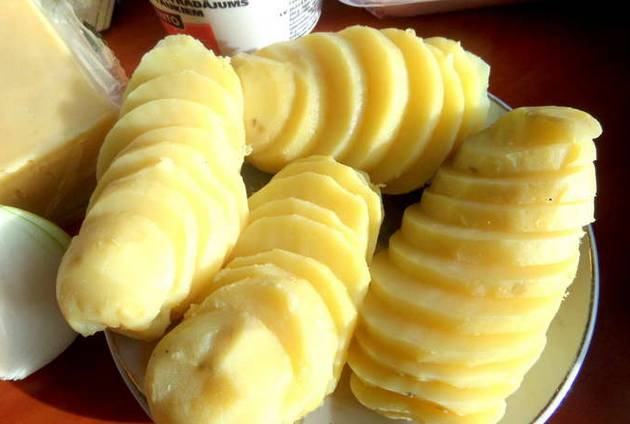 Картофель очищаем и отвариваем до готовности. Затем даем ему остыть и нарезаем тонкими кружочками.