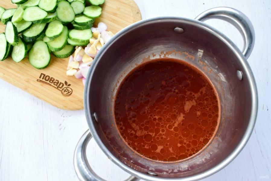 Для маринада в кастрюле соедините воду, томатный соус, масло, сахар и соль. Доведите до кипения. Огурцы нарежьте кружками толщиной 0,5 см, лук и чеснок — ломтиками.