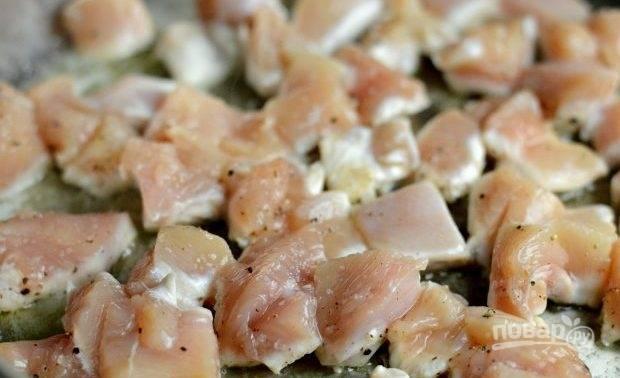 1. В большой глубокой сковороде разогрейте оба вида масла. Выложите в него курицу, нарезанную кубиками. Обжарьте её в течение 5 минут, пару раз перевернув.