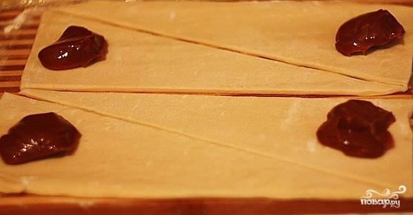 Разморозьте слоёное тесто, раскатайте его. Разрежьте на большие треугольники. Сгущёное молоко перемешайте с топлённым сливочным маслом. Выложите по чайной ложки массы из сгущёного молока и масла на край треугольников.