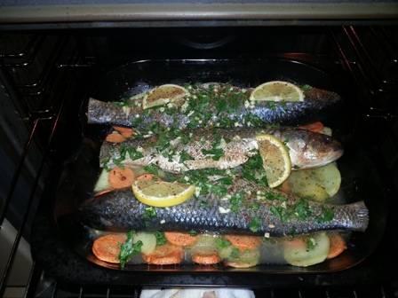 Смазываем противень маслом и выкладываем подготовленные овощи, сбрызгиваем соком половинки лимона, солим и перчим. Выкладываем рыбу, на рыбку выложим кусочки лимона. Запекаем в разогретой до 200 градусов духовке минут 50. Рыбу можно минут через 20-30 перевернуть на другую сторону.