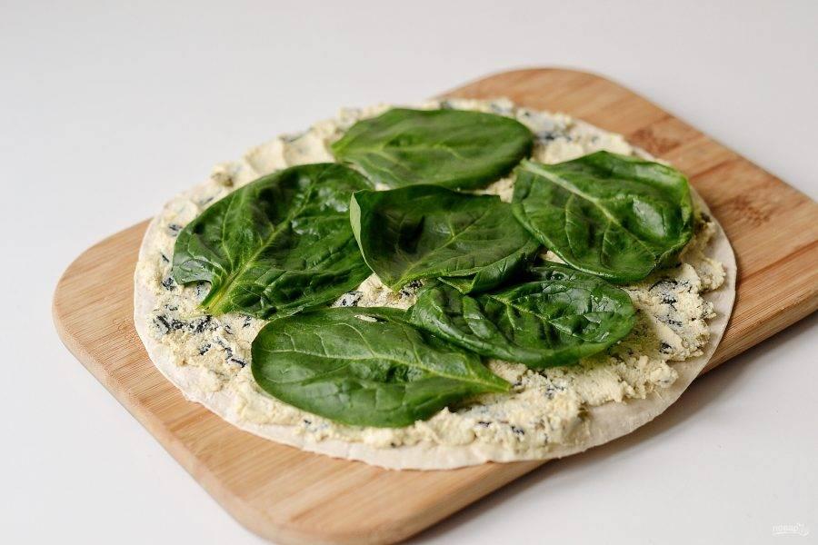 Нанесите начинку равномерным слоем на лаваш. Сверху выложите листья шпината. Скрутите рулет, заверните его в фольгу и уберите на пару часов в холодильник настояться.
