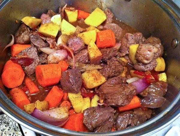 6. Выложить все ингредиенты в сотейник, добавив еще соли и перца по вкусу. Влить красное сухое вино.