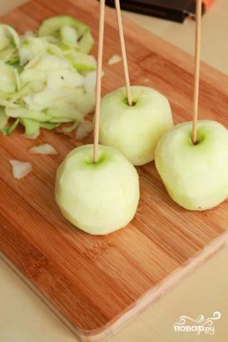 Яблоки очищаем от кожуры. Постарайтесь, чтобы очищенные яблоки были как можно более круглыми. Вставляем в каждое яблоко по шпажке, как показано на фото.