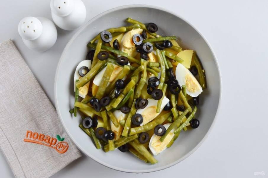 Оливки порежьте кольцами. Украсьте салат.