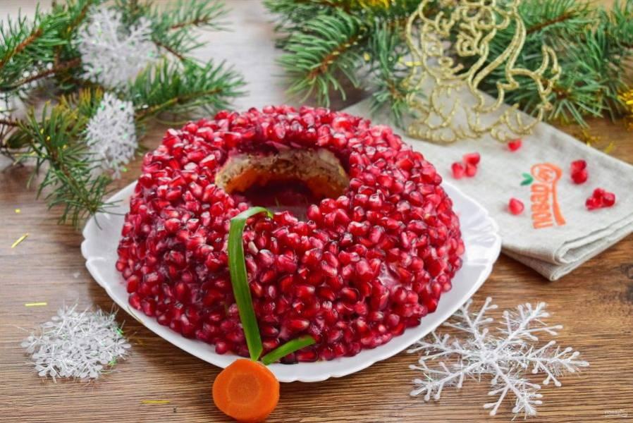 Верх салата покройте зернами граната. Аккуратно вытащите стакан. Концы зеленого лука соедините и прижмите кружком моркови. Дайте салату настояться и подавайте к столу. Счастливого Нового года!