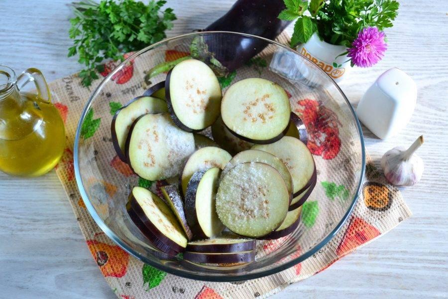 Выложите нарезанные баклажаны в большую миску, посыпьте солью и перемешайте. Оставьте на 20-30 минут, затем слейте выделившуюся жидкость, а баклажаны промойте.