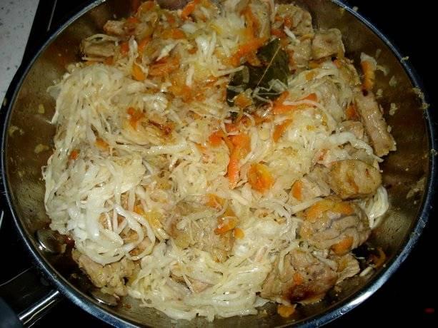 Отжимаем квашеную капусту и отправляем ее также на сковородку через пару минут после моркови, добавляем лавровый лист, перемешиваем все и тушим минут 15.