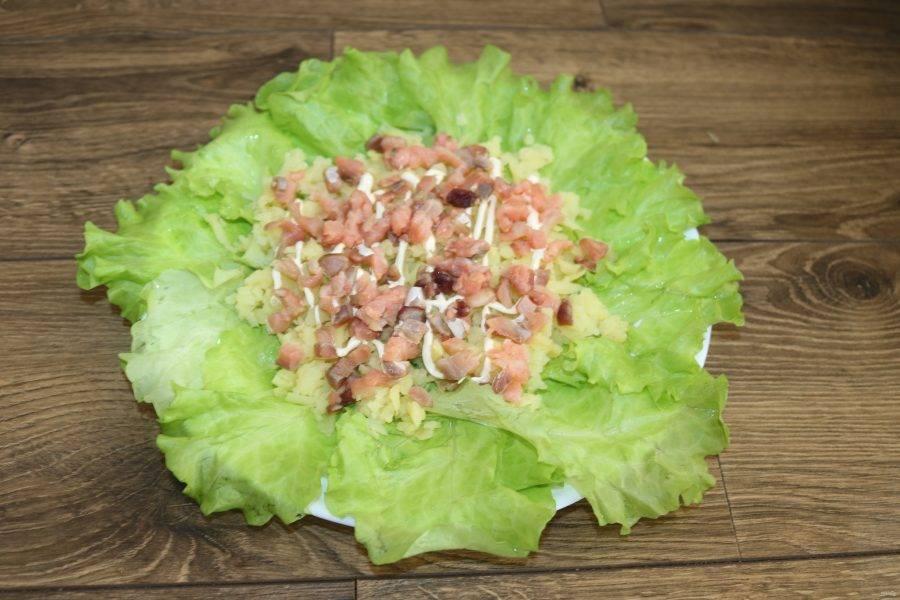 Далее выложите кусочки нарезанной рыбы, сверху сделайте сеточку майонеза.
