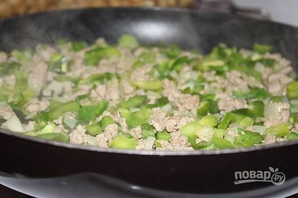 2. На сковороде тем временем обжарьте лук с чесноком и перцем пару минут. Добавьте фарш и жарьте на среднем огне, помешивая.