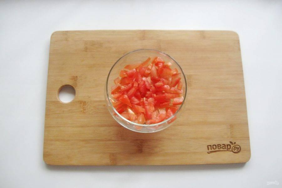 Помидор помойте и мелко нарежьте. Выложите первым слоем салата.