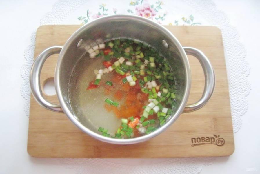 В кастрюлю налейте куриный бульон и выложите нарезанные овощи.