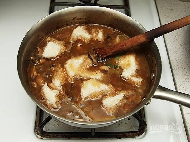 Когда бульон прокипел отведенное время, уберите из него листы лавра и тимьян. Поломайте скибки хлеба на небольшие кусочки и отправьте их в суп. Дайте хлебу размокнуть в течение 30 секунд.