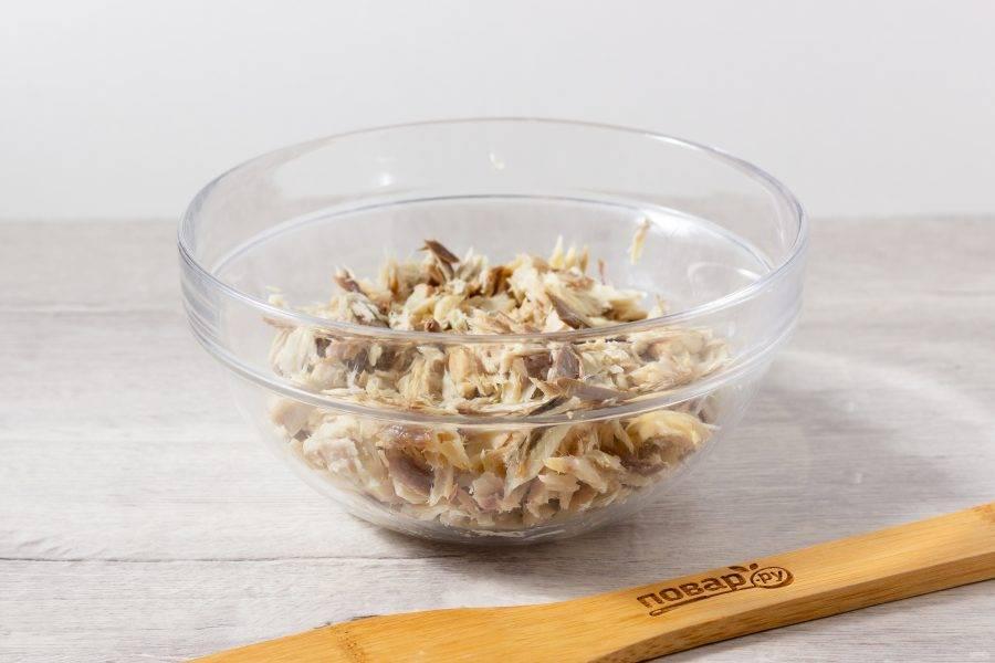 Рыбу тщательно отделите от костей и кожи, порвите небольшими кусочками и выложите в салатник.