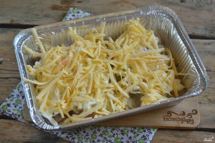 Сверху смажьте майонезом и положите слой натертого на крупной терке твердого сыра. Запекайте рыбу в разогретой до 200°С духовке 35-40 минут. Когда с сыра и майонеза образуется золотистая корочка, блюдо можно вынимать и подавать к столу.