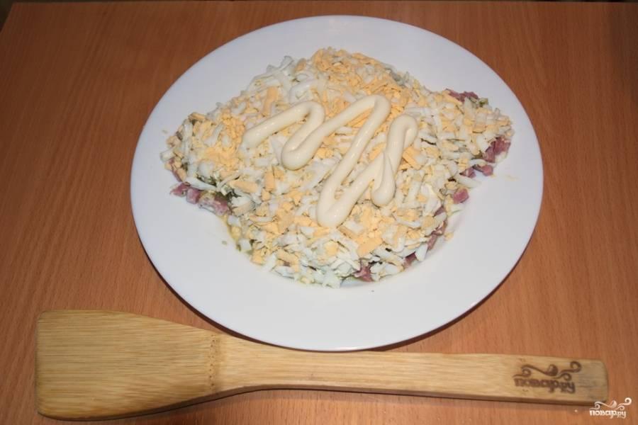 Натрите на терке яйца. Смажьте  огуречный слой майонезом. Выложите на него яйца. Распределите равномерно. Натрите на терке твердый сыр. Яичный слой смажьте майонезом, а сверху выложите сырный слой.
