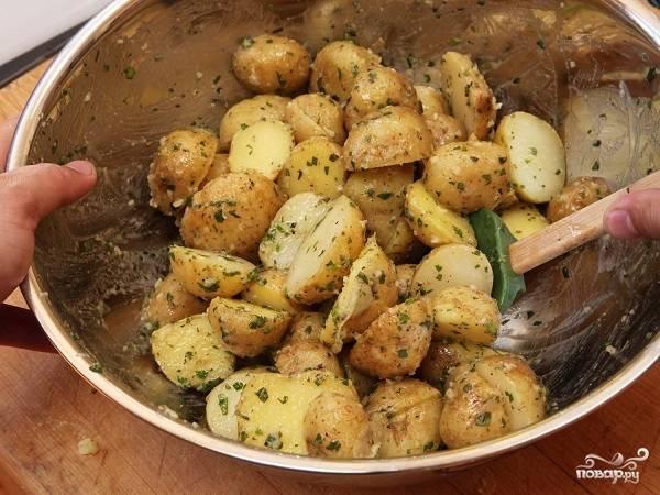 2. Слейте воду, а картофель остудите немного. Затем нарежьте каждую картофелину пополам, выложите в глубокую мисочку. Добавьте примерно половину от общего количества орегано, петрушки и измельченного чеснока. Посолите по вкусу, сбрызните оливковым маслом. Перемешайте как следует. Лучше всего делать это небольшими порциями, чтобы картофель как следует соединился со специями и маслом.