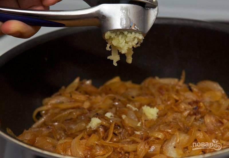 Уменьшите температуру. Очистите чеснок и отправьте его в сковороду с луком, перемешайте и обжарьте в течение, примерно 1 минуты.