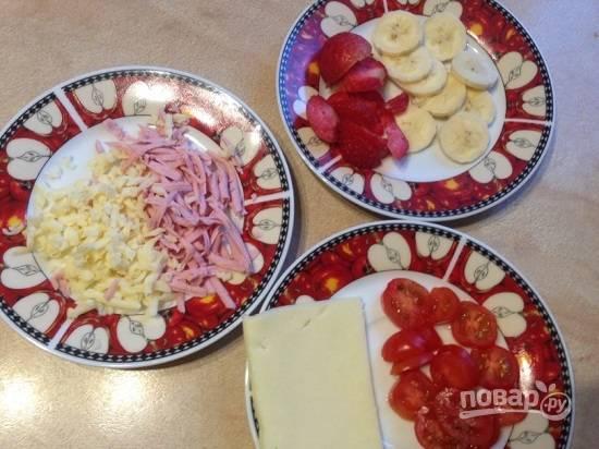 А пока займемся начинками. Колбасу и половину сыра натираем на крупной терке. Очистим банан и нарежем его вместе с клубникой, на маленькие кружочки нарежем помидорки.