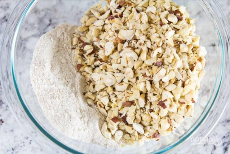 2.Очистите и слегка поджарьте нарезанные крупно орехи, выложите их в миску и перемешайте.