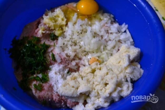 В небольшой посуде соединяем все подготовленные продукты: фарш, зелень, соль, перец, мускатный орех, яйцо, чеснок, лук и хлеб, не забыв его отжать от воды.