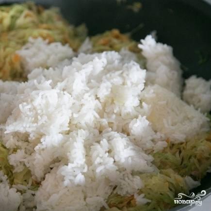 Сразу вслед за этим добавляем в блюдо отваренный до готовности рис.