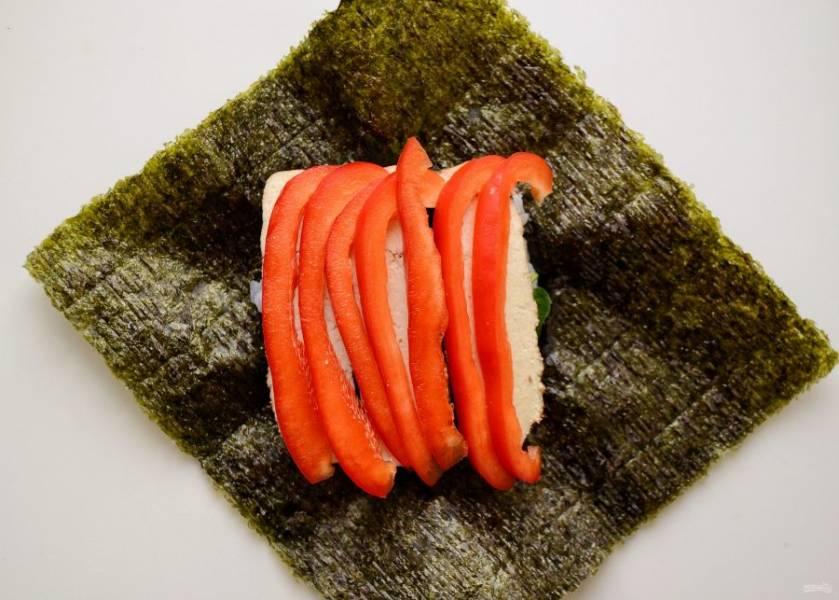 Выложите на тофу кусочки красного перца. Чем плотнее они будут лежать, тем красивее получится онигирадзу в разрезе.