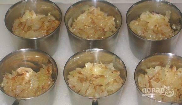 В кокотницы выложите половину от всех обжаренных грибов. Сверху выложите карамелизированный лук, равномерно его распределив.