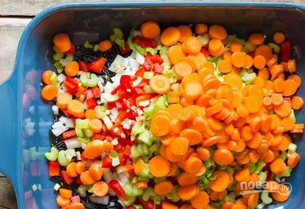 1. Подготовьте большую жаропрочную форму. Духовку разогрейте до 180 градусов. Выложите в форму рис, мелко нарезанную морковь, лук, перец, сельдерей, чеснок.