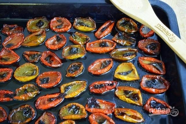 Затем уменьшите температуру до 100°C и продолжайте вялить томаты еще 2-3 часа до нужного вам состояния. Томаты должны хорошо подвялиться и сморщиться, но не подгореть снизу.
