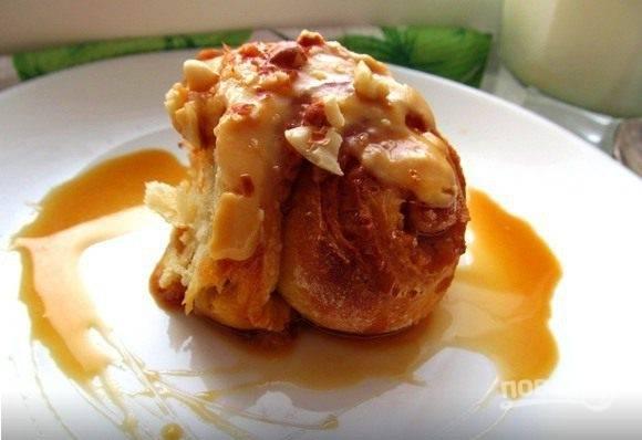 Горячие булочки залейте карамельным кремом. Добавьте измельчённые орехи. Во время подачи, украсьте булочки оставшейся карамелью. Приятного чаепития!
