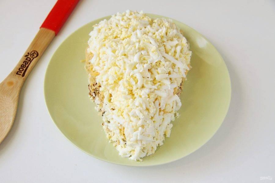 Смажьте сыр майонезом и выложите слой из вареных яиц.