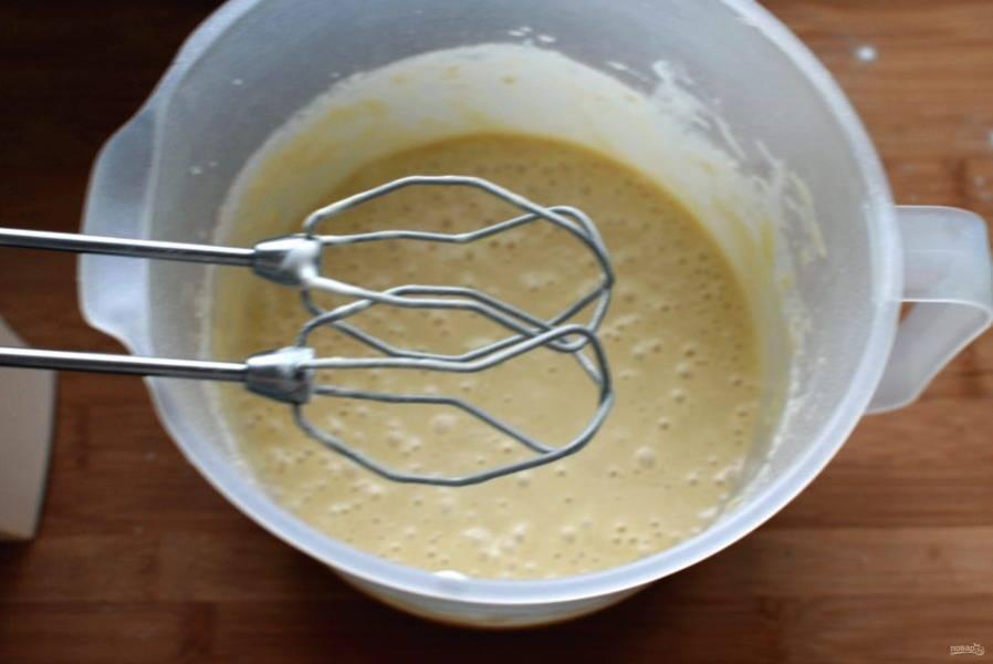 Влейте молоко, добавьте растопленное и охлажденное сливочное масло. Сверху всыпьте просеянную с разрыхлителем муку и миксером на низкой скорости перемешайте тесто. Оно получается довольно жидким, как оладьевое.